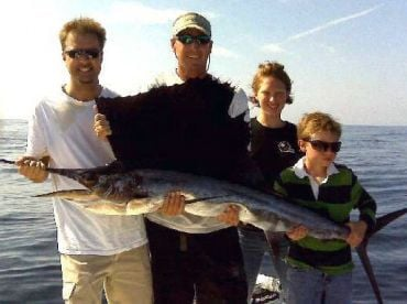 Excited family holding their first sailfish thanks to Capt Jason.