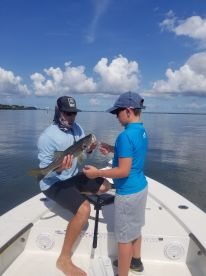 Captain Nick showing him how to hold the fish